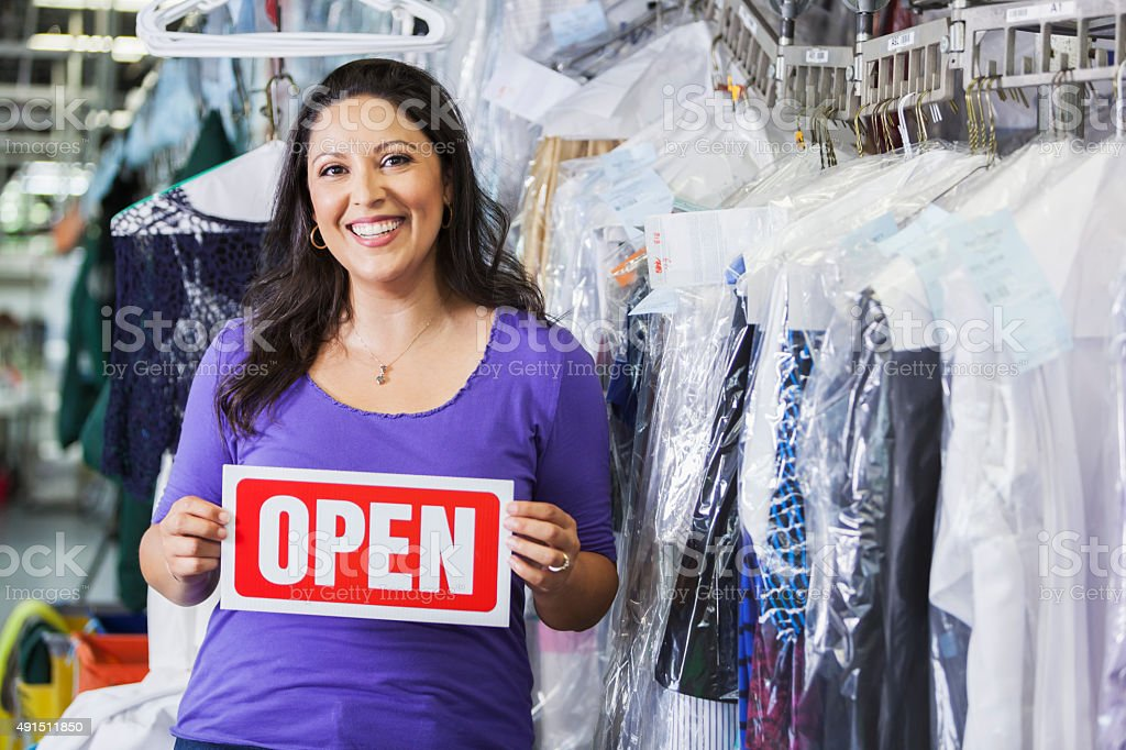 Hispanic woman working in dry cleaners with OPEN sign stock photo