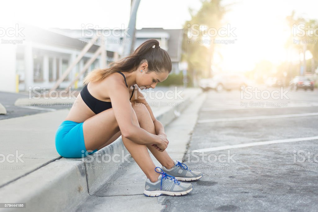 Hispanic Women Resting On The Street After Her Run stock photo
