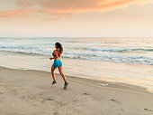 Hispanic Women Running At The Beach At Sunset