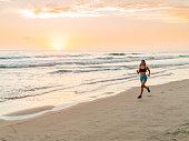 Hispanic Women Running At The Beach At Sunset