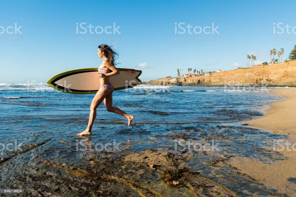 Hispanic Women Running With Her Surboard stock photo