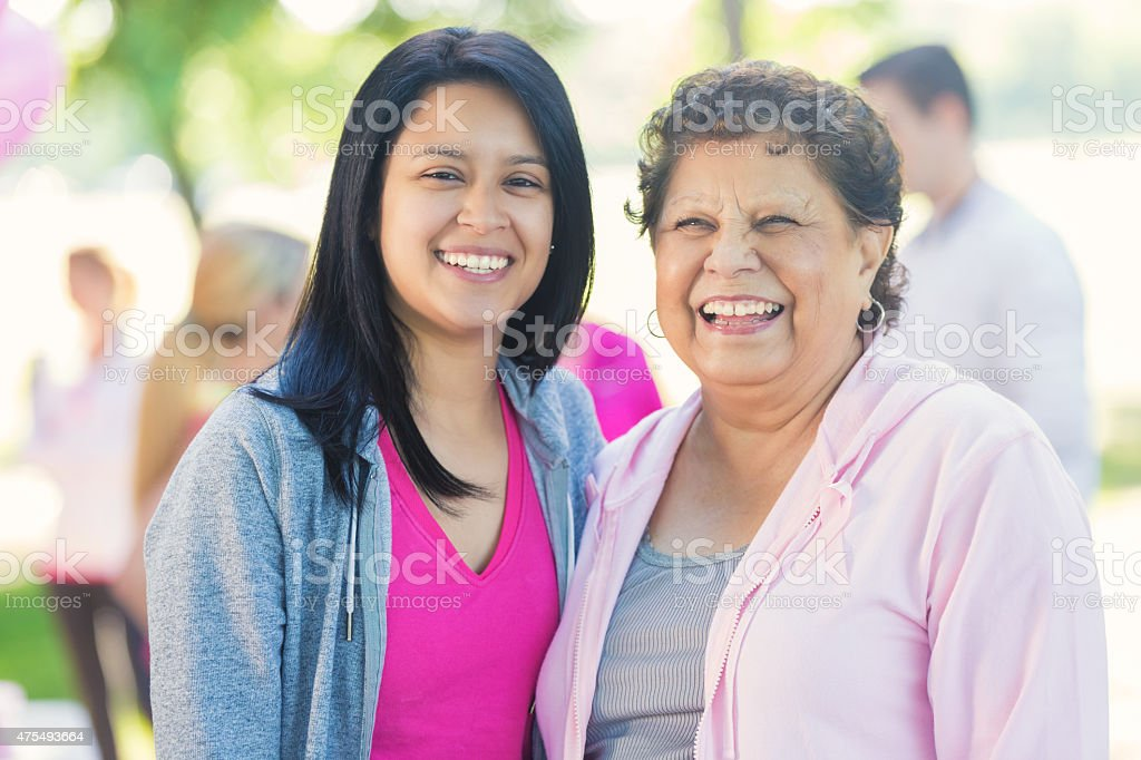 Hispanic women smiling after registering for breast cancer awareness race stock photo