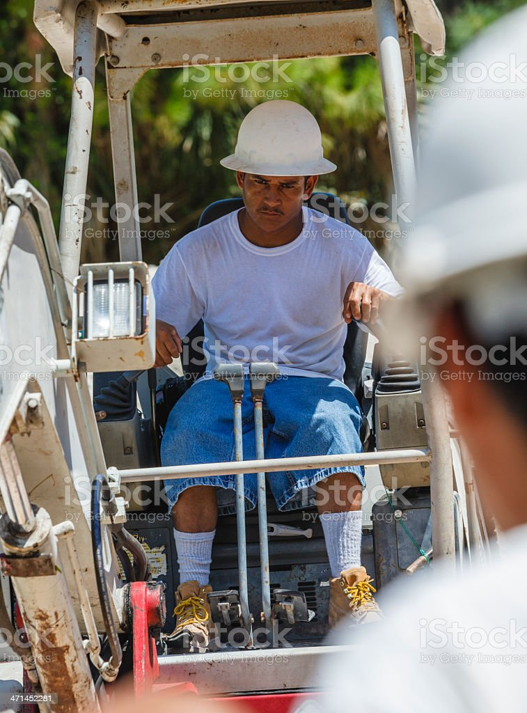 Hispanic Worker Operates Backhoe on Construction Site royalty-free stock photo