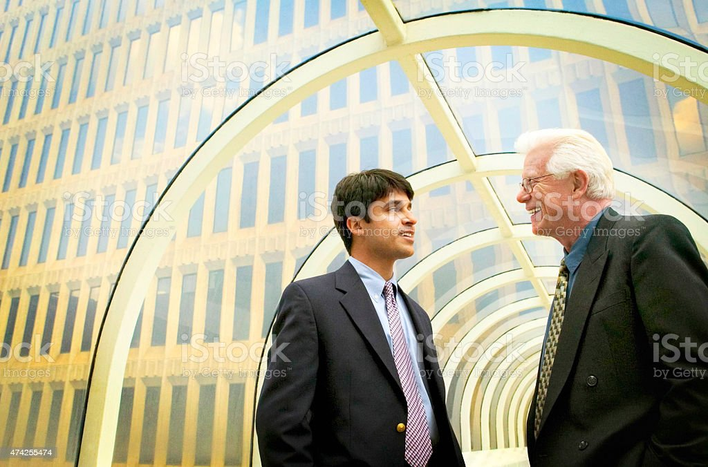 Hispanic young businessman consulting with senior businessman. stock photo