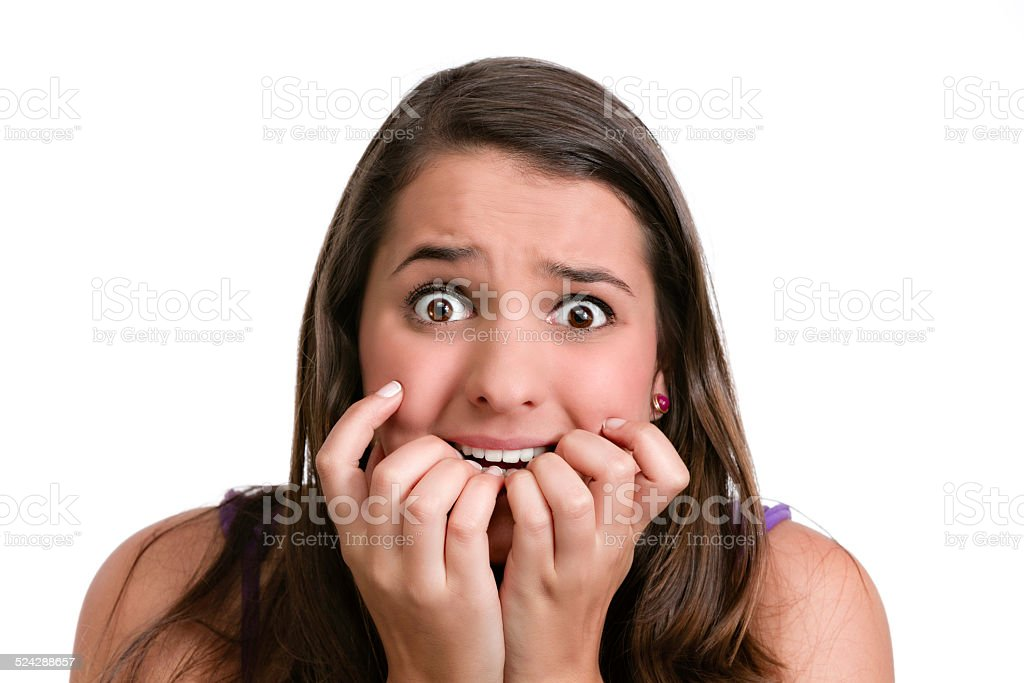 Hispanic young woman terrified and biting nails stock photo