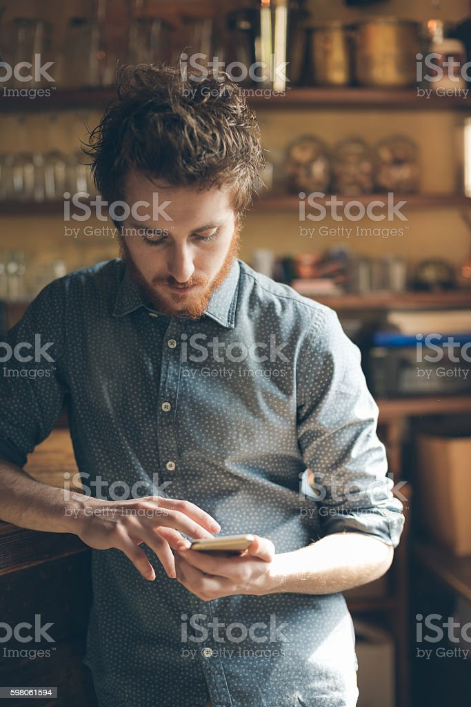 Hispter guy with mobile phone in the bar stock photo