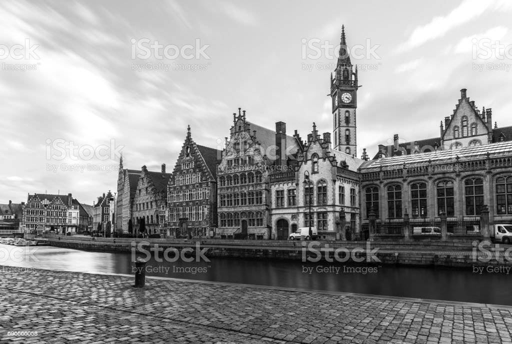 Historic buildings, old clock tower and water canal in medieval Belgian city of Gent (Ghent is a port city in northwest Belgium), popular tourist destination in Europe, black and white photography stock photo