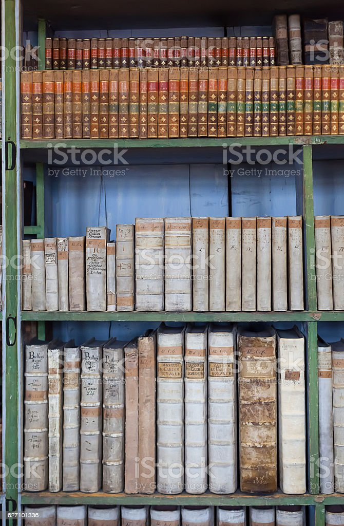 historic old book in library, wooden bookshelf stock photo
