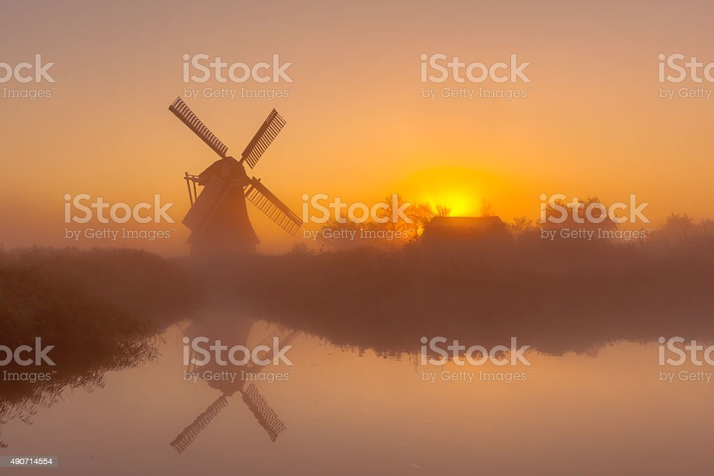 Historic windmill along a canal stock photo