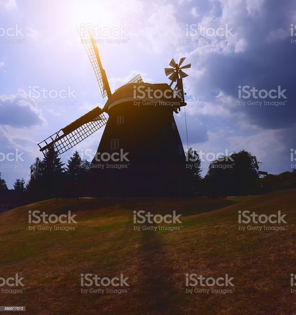 historic windmill in backlit stock photo
