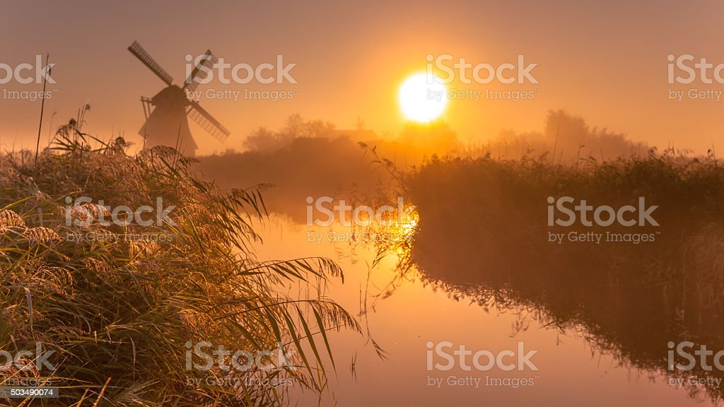 historic windmill on a foggy morning stock photo