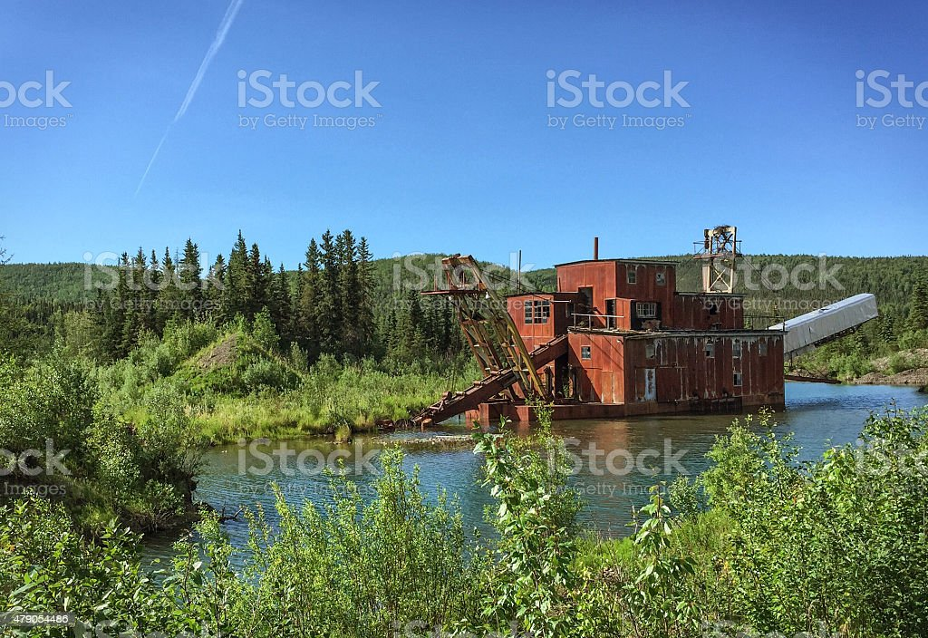 Historical Alaska Gold Dredge with Green Grass in Summer stock photo