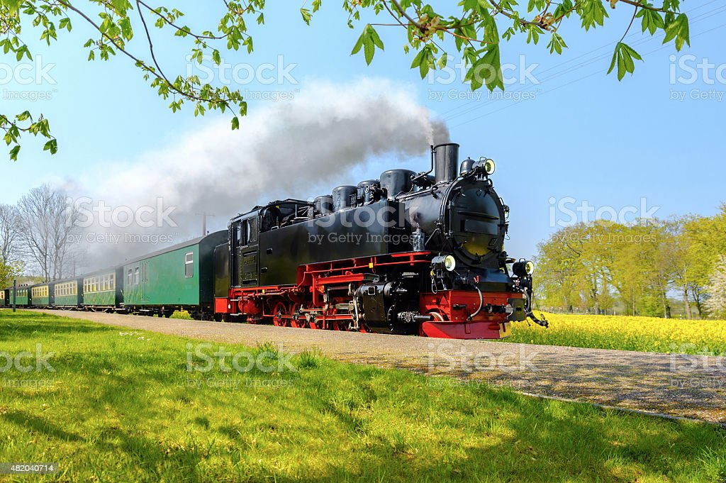 Historical German steam train passes through the fields in sprin stock photo