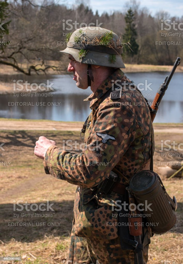 Historical reconstruction of the battles of World War II. A participant in the reconstruction in the form of a Wehrmacht soldier before the start of the battle. stock photo