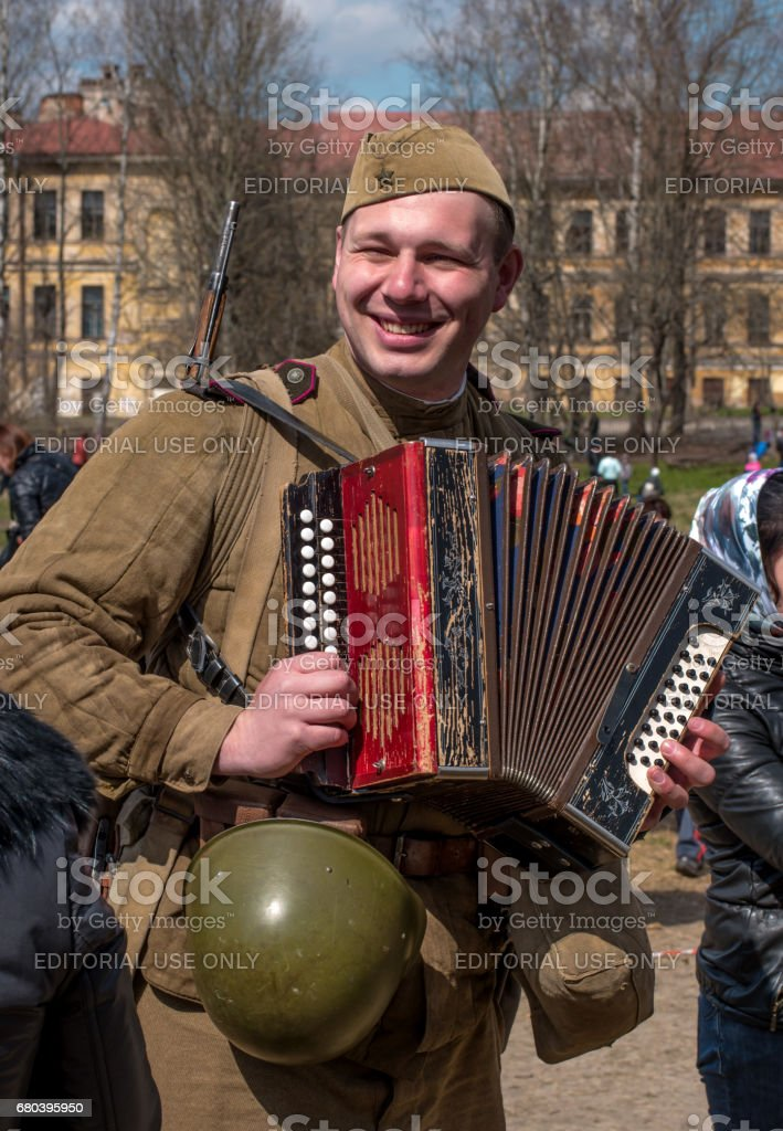 Historical reconstruction of the battles of World War II. A Soviet soldier plays the accordion and sings funny songs. stock photo