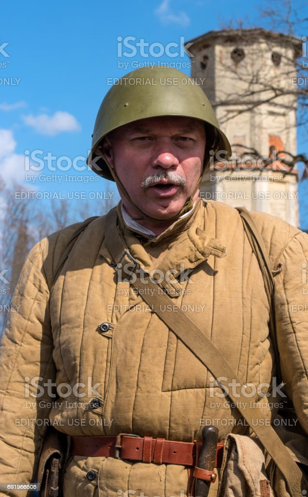 Historical reconstruction of the battles of World War II. A Soviet army soldier in a quilted jacket and a helmet. stock photo