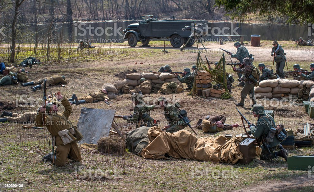 Historical reconstruction of the battles of World War II. German soldiers defend a mortar battery. The dead Soviet soldier falls. stock photo