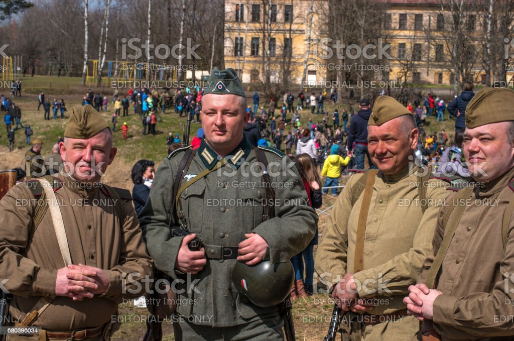 Historical reconstruction of the battles of World War II. German and Soviet soldiers after the battle - photographing for memory. stock photo