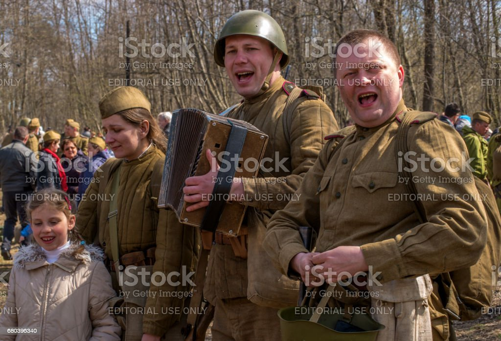Historical reconstruction of the battles of World War II. Soldiers sing the song of the war - Katyusha. The soldier plays the accordion. stock photo