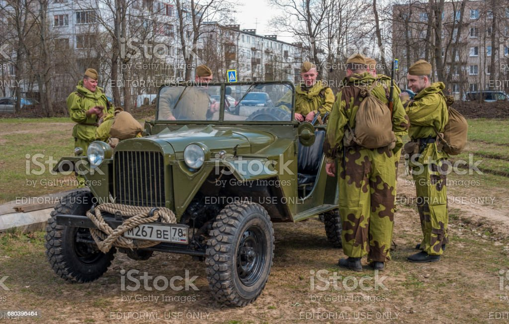 Historical reconstruction of the battles of World War II. Soviet soldiers in camouflage suits near a military jeep GAZ 67B. stock photo