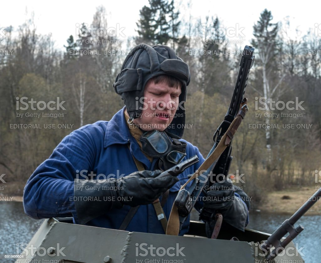 Historical reconstruction of the battles of World War II. The driver of the armored car. Dressed in overalls and a tank headset. stock photo