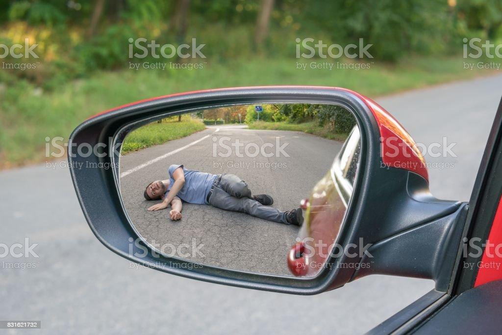 Hit and run concept. View on injured man on road in rear mirror of a car. stock photo