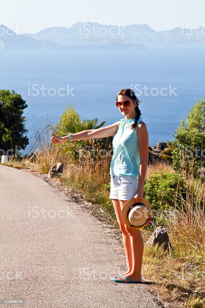Hitchhike girl in the road with the sea and mountains stock photo