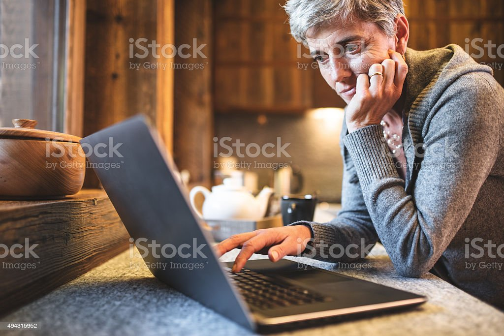 hitech senior woman surfing on the kitchen stock photo