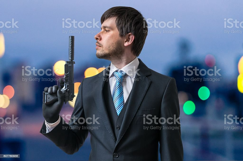 Hitman or assassin holds pistol with silencer in hand stock photo
