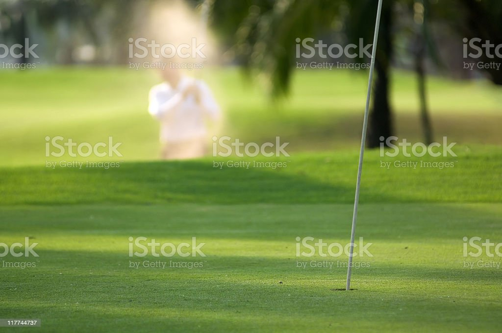 Hitting golf ball from sand trap  into the hole stock photo