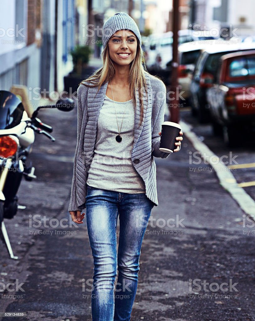 Hitting the city sidewalks with a coffee in hand stock photo