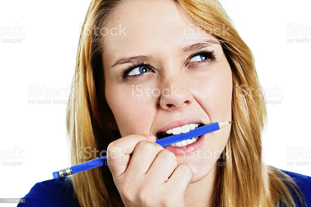 Hmmmm, I wonder! Pretty blonde thinks, chewing pencil royalty-free stock photo