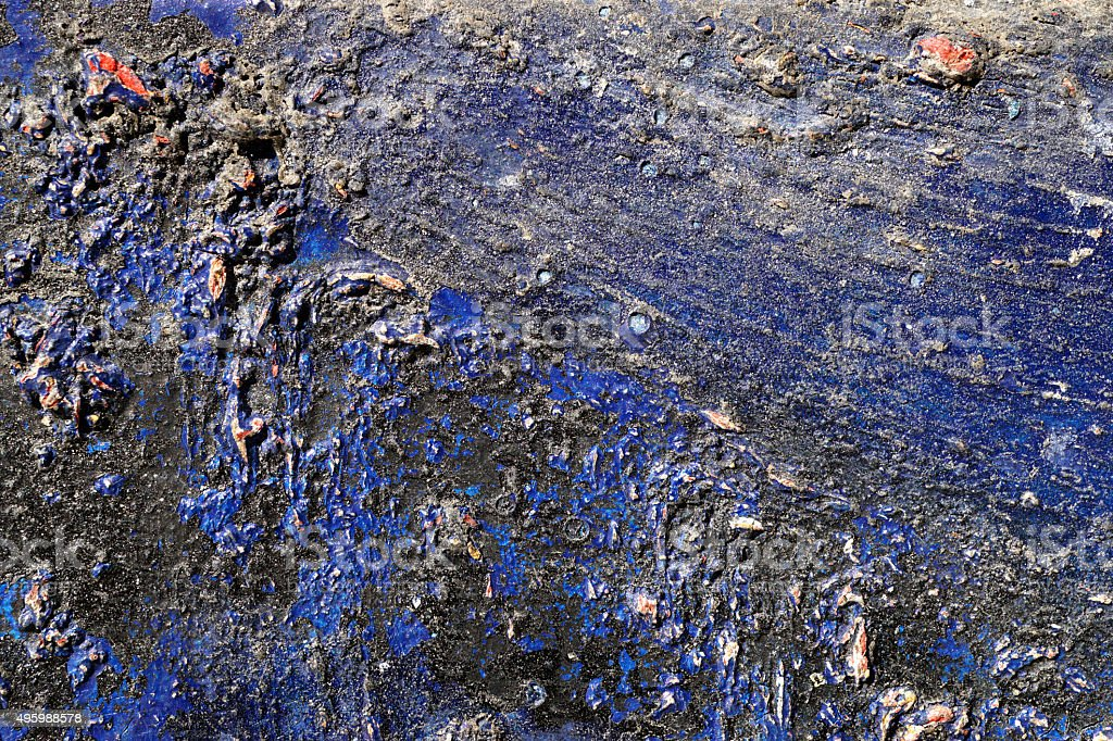Hoarse, scratched and peeled surface  with blue and black paint stock photo