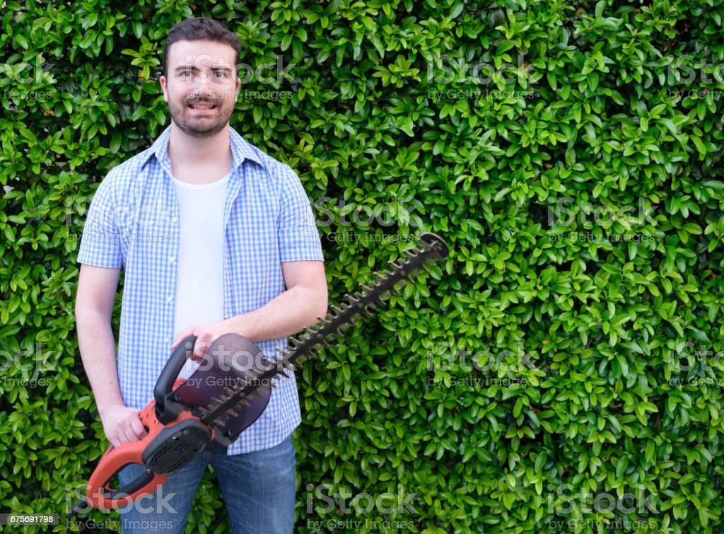 Hobbyist  gardner  using an hedge clipper in the home garden stock photo