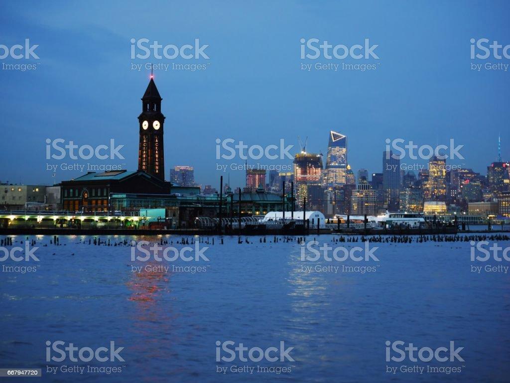 Hoboken Lackawanna clock tower, NJ transit, Path, light rail terminal and Midtown Manhattan in background at dusk stock photo