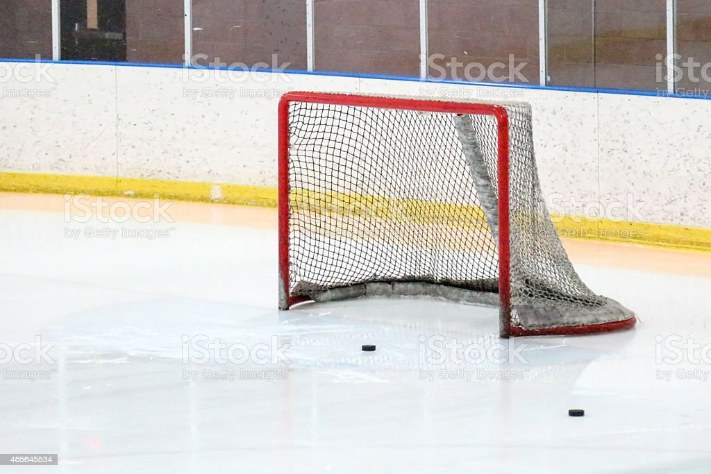 Hockey net and two pucks at an indoor hockey rink stock photo