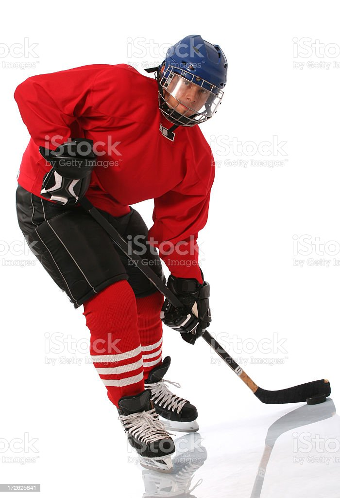 Hockey player in red and blue aiming to take shot of puck stock photo