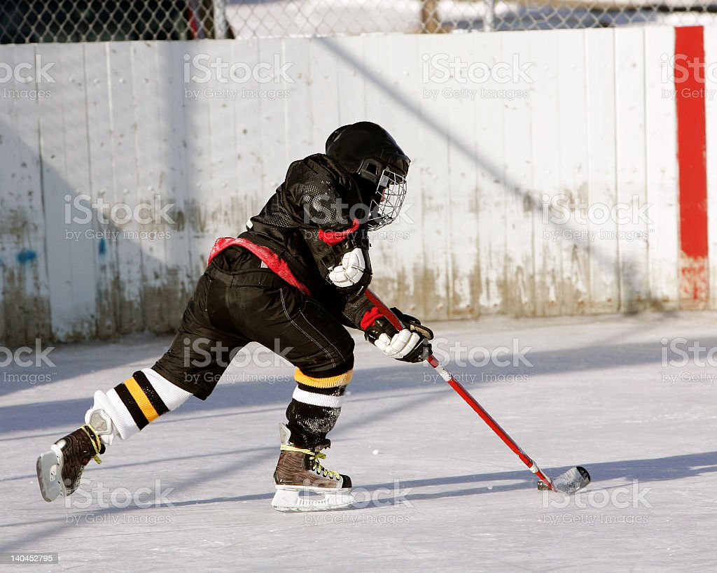 Hockey player with full gear and puck on pond royalty-free stock photo