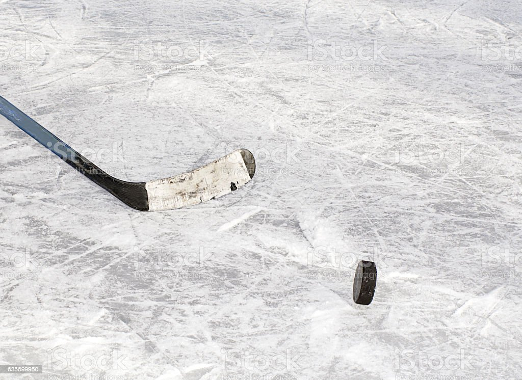 Hockey puck and stick on ice stock photo