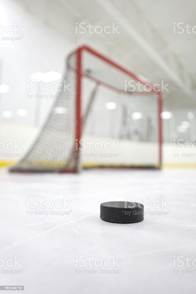 Hockey Puck at Ice Level Near Goal stock photo