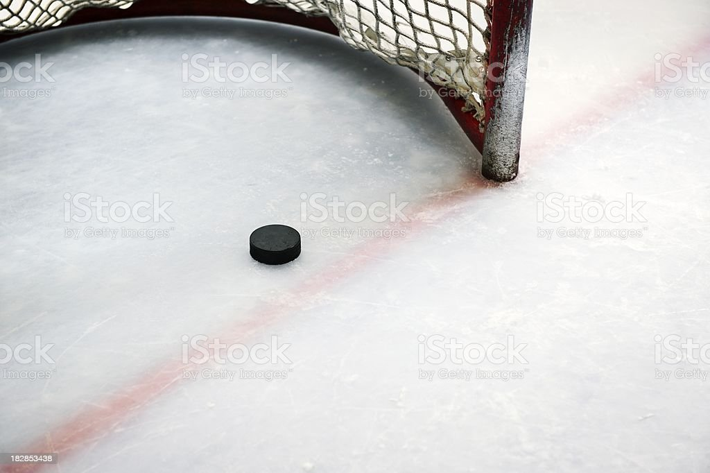 Hockey puck in goal and red line stock photo
