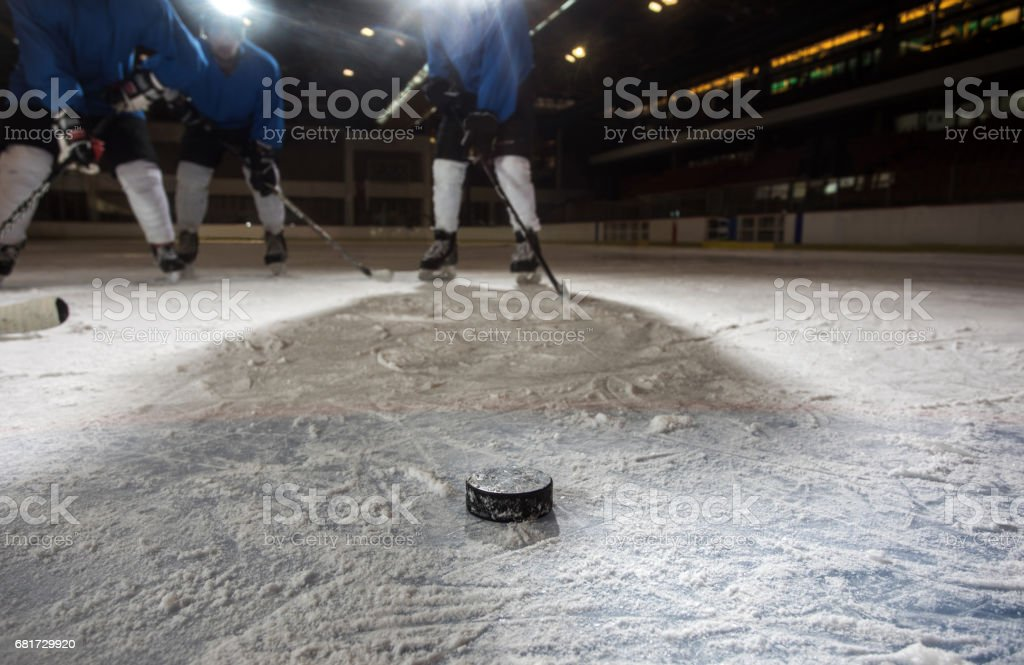 Hockey puck in ice hockey arena with players in the background. stock photo