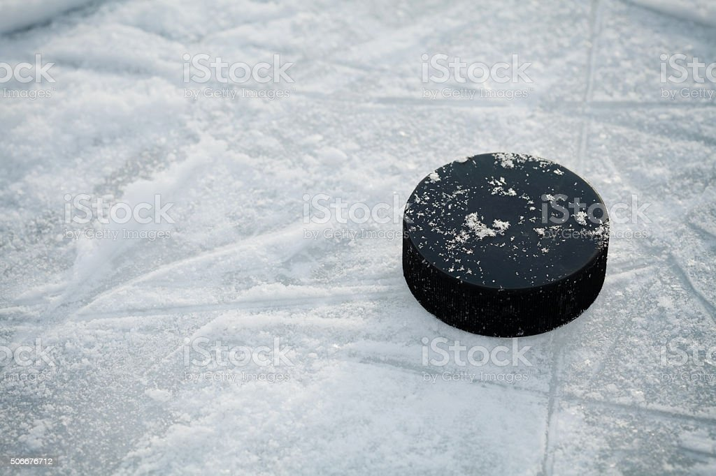 Hockey puck on ice hockey rink stock photo