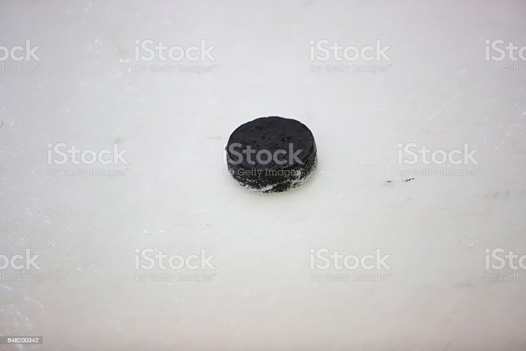 black hockey puck on ice of ice hall