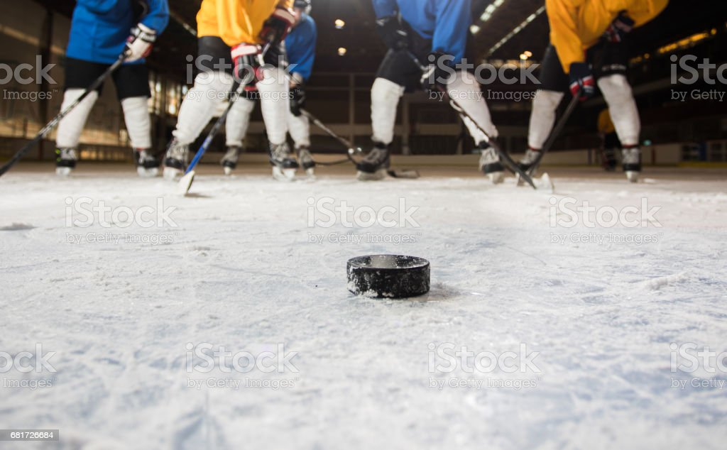 Hockey puck with ice hockey players in the background. stock photo