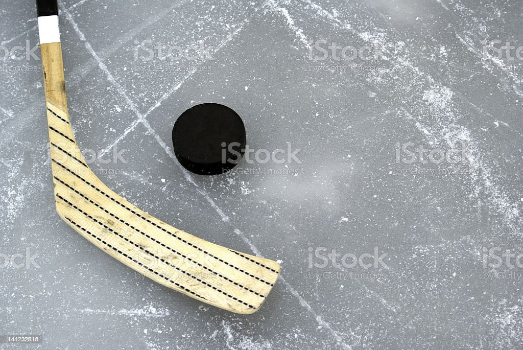 Hockey stick and black puck on ice royalty-free stock photo