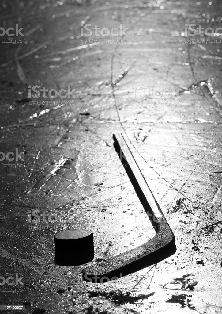 Hockey Stick and Puck on Pond Ice Rink Outside stock photo