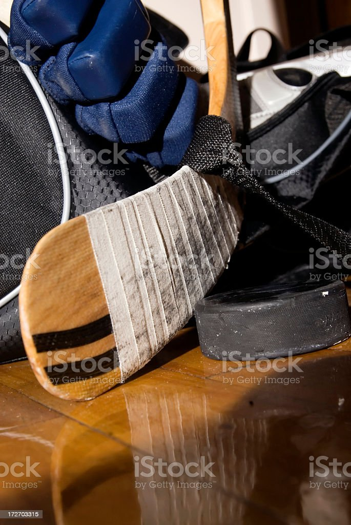 Hockey equipment left to dry on a wooden floor after a hockey game.