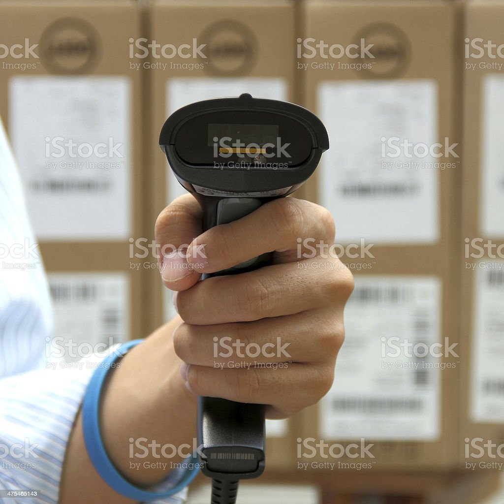 Hoding barcode scanner over the boxes background stock photo