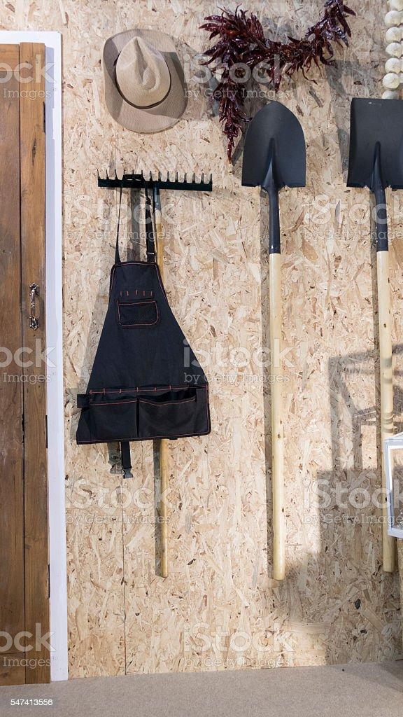 hoe, shovel, harrow and hat beside wooden door stock photo